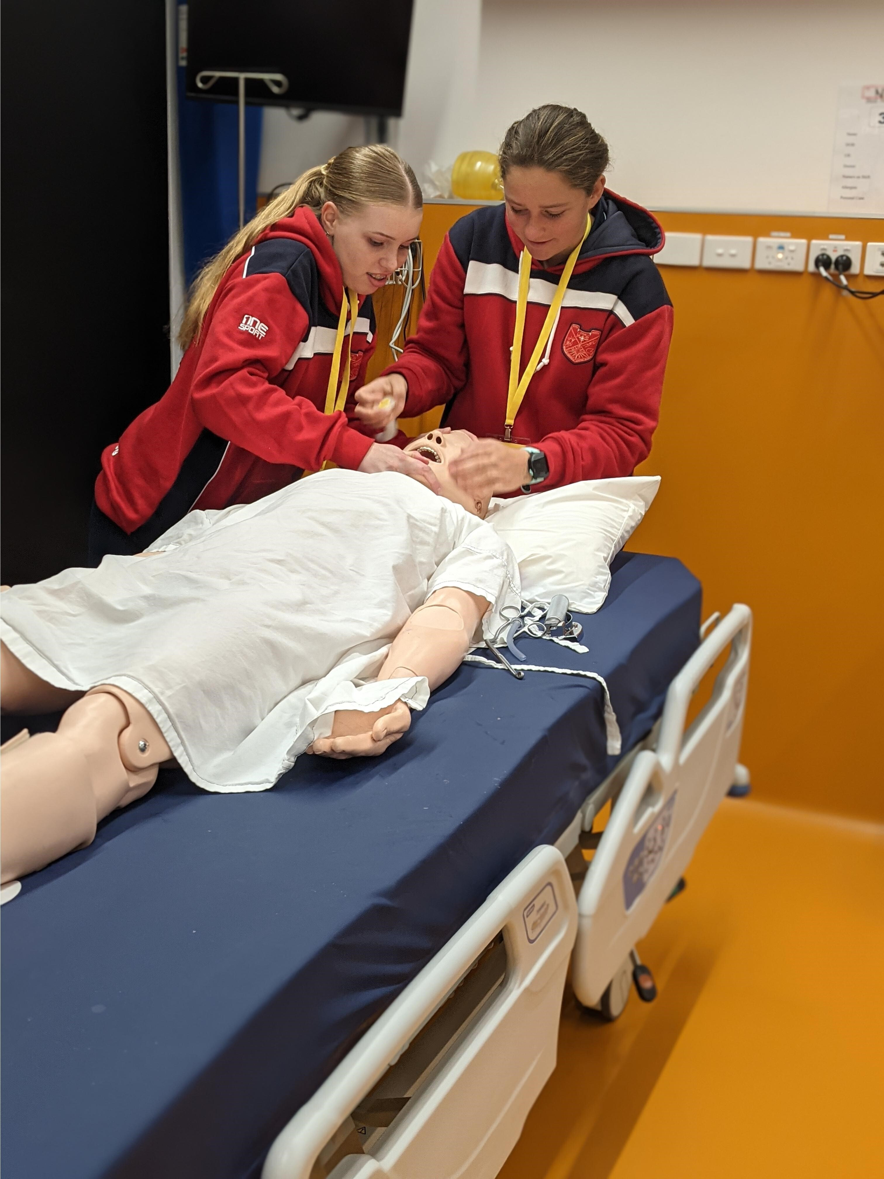 Ruby Carr and Lottie McMahon successfully resusitate a patient at the recent University Promotion Day in Canberra.
