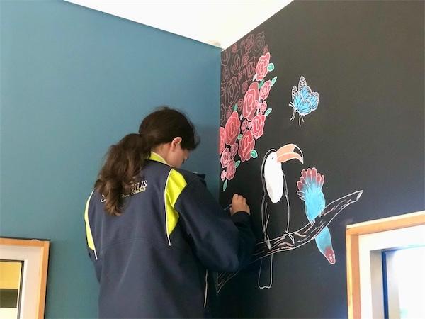 Bella Wood working on her chalk mural